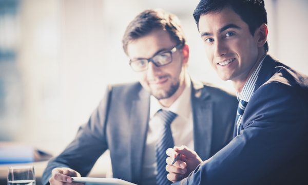 Image of smart young businessmen looking at camera at meeting